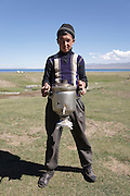 A young man carries a samovar (Russian style tea urn) near lake Song Köl, Kyrgyzstan