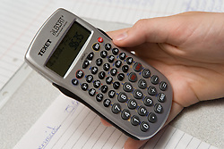 Close up of students hand using calculator to work out average results of an experiment,