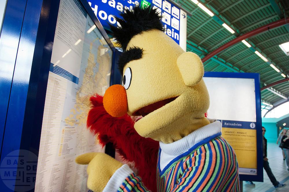 Bert kijkt op een bord van de NS welke trein hij moet pakken. Een deel van de cast van de musical Het Beste van Sesamstraat doet Utrecht Centraal aan tijdens de promotietoer van de voorstelling.<br /> <br /> Bert is looking for the right train at Utrecht CS. Characters of the musical The Best of Sesame Street are visiting the main train station in Utrecht for promotion.