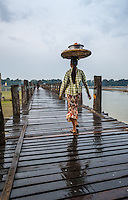 MANDALAY, MYANMAR - CIRCA DECEMBER 2013: Woman crossing the U Bein Bridge in Amarpura