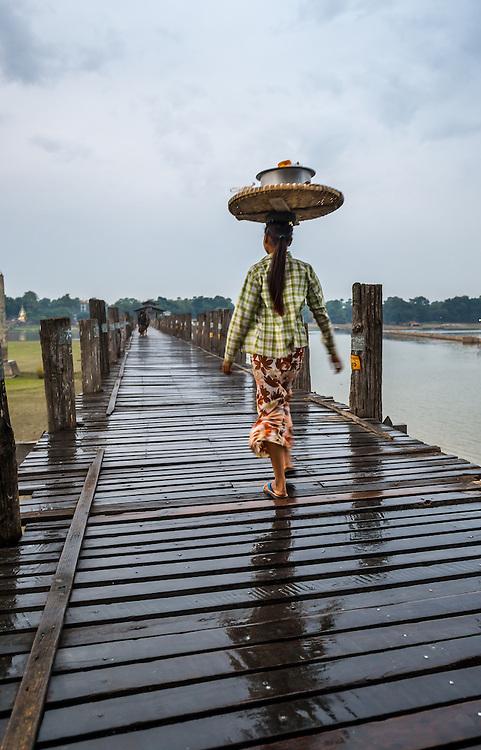 MANDALAY, MYANMAR - CIRCA DECEMBER 2013: Woman crossing the U Bein Bridge in Amarpura