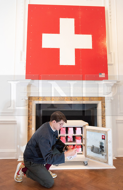 "© Licensed to London News Pictures. 05/10/2018. London, UK. Art installation titled Swiss Passport Office by American artist Tom Sachs. The 24h live performance Swiss Passport Office is on show at the Galerie Thaddaeus Ropac. Those wishing to purchase a passport will be photographed and have their name hand-typed onto a serial-numbered passport issue, stamped with a Studio endorsement and entered into the permanent database. Passports cost €20 (no British pounds will be accepted). Swiss Passport Office encompasses contemporary concerns relating to Brexit, Syria and Trump's immigration policies and their challenge to the notion of global citizenship. ""To effect change, we must first imagine the world not the way it is, but the way we want it to be,"" Sachs says. Photo credit: Ray Tang/LNP"