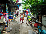 07 JUNE 2017 - BANGKOK, THAILAND:   A resident of Pom Mahakan sweeps the sidewalk in front of her home. Bangkok city officials are expected to tear the structure down in coming weeks. The final evictions of the remaining families in Pom Mahakan, a slum community in a 19th century fort in Bangkok, have started. City officials are moving the residents out of the fort. NGOs and historic preservation organizations protested the city's action but city officials did not relent and started evicting the remaining families in early March.         PHOTO BY JACK KURTZ