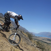 Justin Worth from Queenstown in action during the New Zealand South Island Downhill Cup Mountain Bike series held on The Remarkables face with a stunning backdrop of the Wakatipu Basin. 150 riders took part in the two day event. Queenstown, Otago, New Zealand. 9th January 2012. Photo Tim Clayton