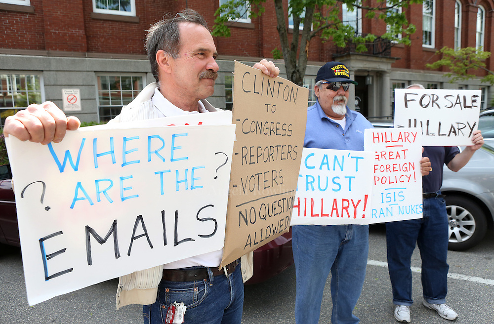 (Exeter, NH - 5/22/15) Brian Griset of Exeter, N.H., left, and Bob Eastman of Exeter, N.H., demonstrate along Water Street as former Secretary of State and presidential candidate Hillary Clinton makes a campaign stop in Exeter, Friday, May 22, 2015. Staff photo by Angela Rowlings.
