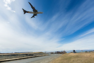 People watch a UPS cargo jet taking off from Ted Stevens Anchorage International Airport at Point Woronzof in Southcentral Alaska with the Chugach Mountains in the background. Spring. Afternoon.