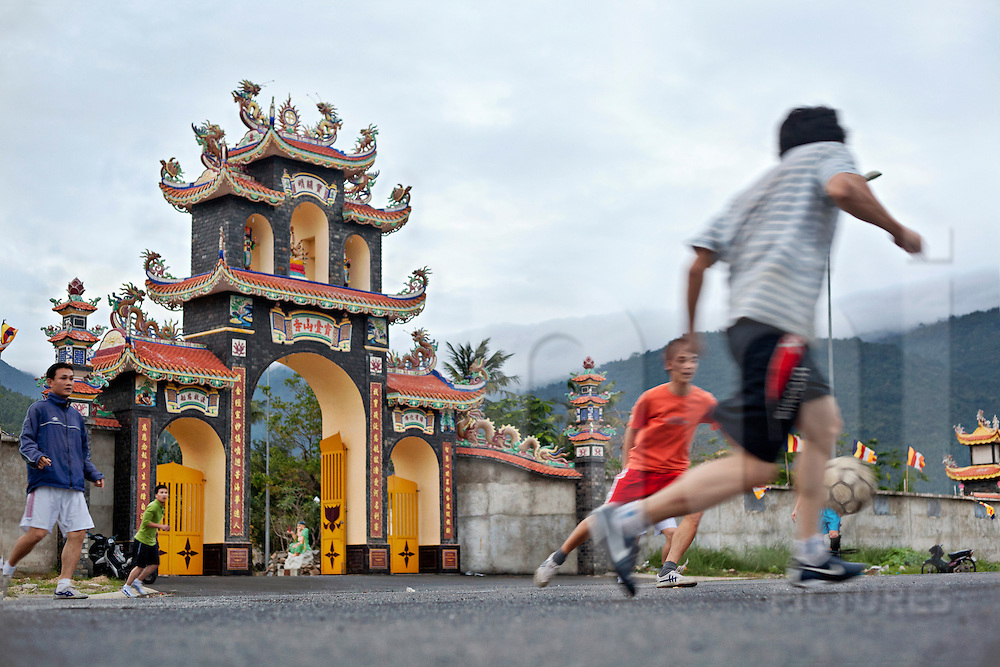 Teenagers play football in front of a pagoda near monkey mountain in Danang city, Vietnam.