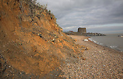 Rapid coastal erosion at East Lane, Bawdsey, Suffolk, England. Soft crag cliffs are easily eroded and washed away by the sea. The historic martello tower has been defended from erosion by rock armour imported from Scandinavia.
