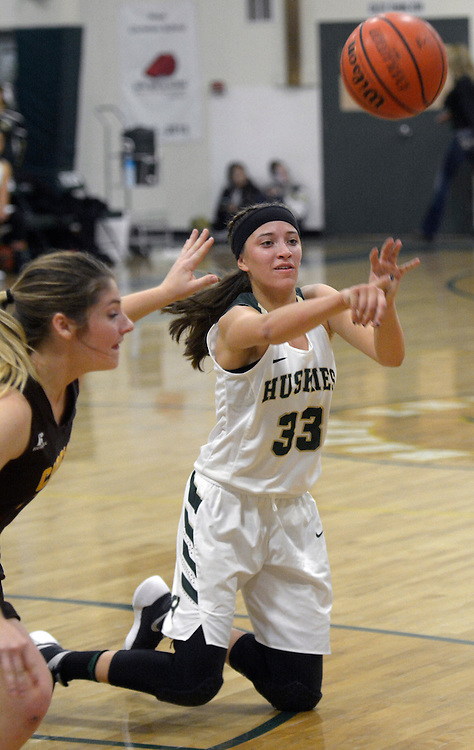gbs112916l/SPORTS -- Hope Christian's Hanna Valencia, passes the ball as she falls to the floor during the game against Cibola at Hope on Tuesday, November 29, 2016. (Greg Sorber/Albuquerque Journal)