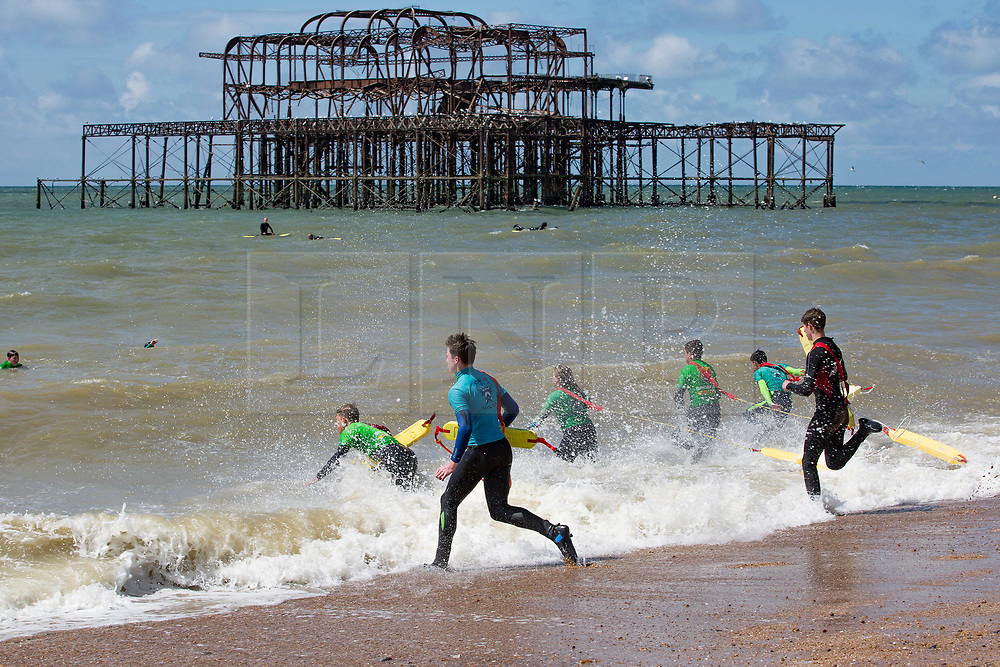 © Licensed to London News Pictures. 20/05/2017. Brighton, UK. Members of the Brighton Surf Life Saving Club brave the still colder seawater to hold their weekly training session and have some fun along the way playing in the sea as sunny weather is hitting the seaside resort. Photo credit: Hugo Michiels/LNP