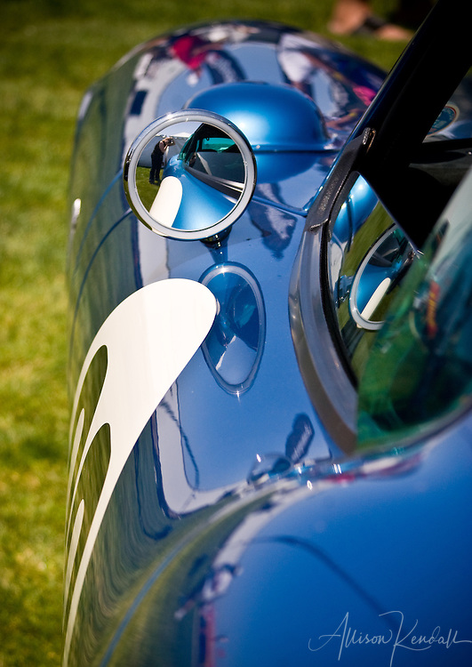 Detail of reflections along the curves of a blue sportscar on display at Laguna Seca during Monterey Car Week