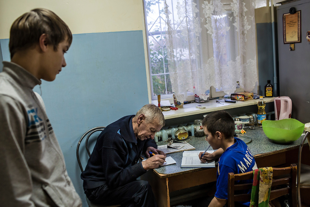 YEKATERINBURG, RUSSIA - OCTOBER 16: Alexandr Fedorovich (C), the live-in supervisor at a facility for at-risk teenage boys run by City Without Drugs, helps one of the boys with his homework on October 16, 2013 in Yekaterinburg, Russia. Nine boys, many of whom were either experimenting with drugs or had dropped out of school, live at the group home, where school attendance and homework are mandatory. City Without Drugs is a well-known narcotics treatment program in Russia founded by Yevgeny Roizman, who was elected mayor of Yekaterinburg in September 2013. (Photo by Brendan Hoffman/Getty Images) *** Local Caption *** Alexandr Fedorovich
