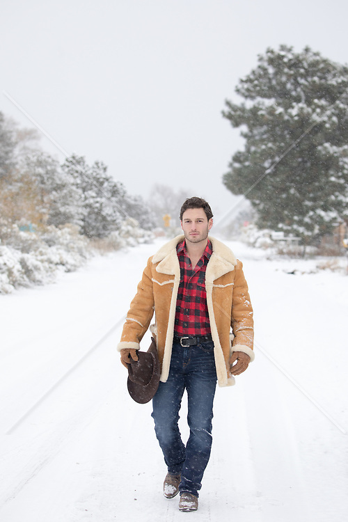 rugged good looking cowboy on a snow covered road
