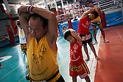 Pre-training stretching excerises for local Thai students at the Rangsit Muay Thai training school. This family owned gym is one of the top schools in Bangkok and has been open for almost 50 years. As well as Thais, every year hundreds of foreign fighters pass through their doors. Some come just to train for fitness, others to enter competitive muay thai events through the schools adjacent boxing stadium where Tuesday night live-to-air fighting events are a weekly occurence..Muay Thai boxing is an ancient fighting form developed in Thailand developed by combining various other forms of SE Asian kickboxing. This brutal sport full of ancient traditions only saw the wearing of modern gloves during training and in boxing matches against foreigners less than 100 years ago where previously only rope-binding of hands was used. Thailand has around 60,000 mauy thai fighters and is the lion's den for anyone wanting to be a success in the sport.