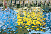 Abstract color reflections in ripples at Nyhavn waterfront canal entertainment district in Copenhagen, Denmark