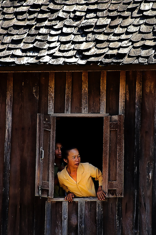 A woman in Hongsa, Laos looking out of a window in her traditional Tai Lhu home.
