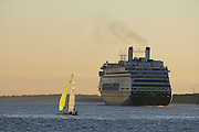 USA, Newport, RI - Cruise ship dwarfs sail boat in Narragansett Bay.
