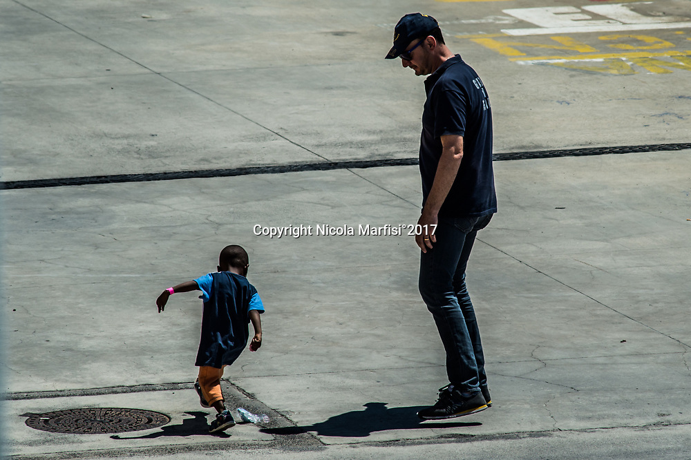 Catania 29-05-2017 Port of Catania, San Giusto Navy ship with aboard 929 migrants saved in several operations and ten dead. Many unmarried women and children, including two very small children. A man of Guardia di Finanza corp and a small baby kicking a plastic bottle right after landing from the Navy's ship.