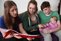 Health visitor visiting teenage couple with baby