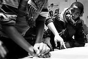 Woluwe-Saint-Lambert. 20 februari 2013 Jongeren bezig met houtsnedes in jongerencentrum Antichambre asbl - Zij zullen na het drukken van de houtsnedes op grote vellen papier, in het mim, muziekinstrumentenmuseum , een performance ondersteunen tijdens de museum nightfever. Jongen kijkt to bij de uitleg.