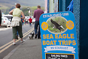 Tourist signage promoting boat trips and tourist exhibits based around the presence of sea eagles, Portree, Skye, Scotland.