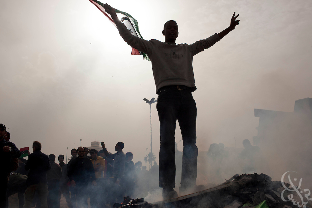A Libyan opposition protester stands atop a burning pile of books and posters during a protest in the eastern city of Benghazi, Libya March 02, 2011. March 02 is traditionally a celebration of the People's Authority Day in Libya, and protesters marked the occasion by burning Qaddafi books, speeches and images. .Slug: Libya.Credit: Scott Nelson for the New York Times
