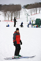 A young woman head to the slopes at the Quechee Ski Hill in Quechee, Vermont. Model Release.