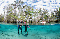 Father and daughter snorkelers pose in the clear spring waters with a kayak in the background. Horizontal orientation split image. Three Sisters Springs, Crystal River National Wildlife Refuge, Kings Bay, Crystal River, Citrus County, Florida USA.