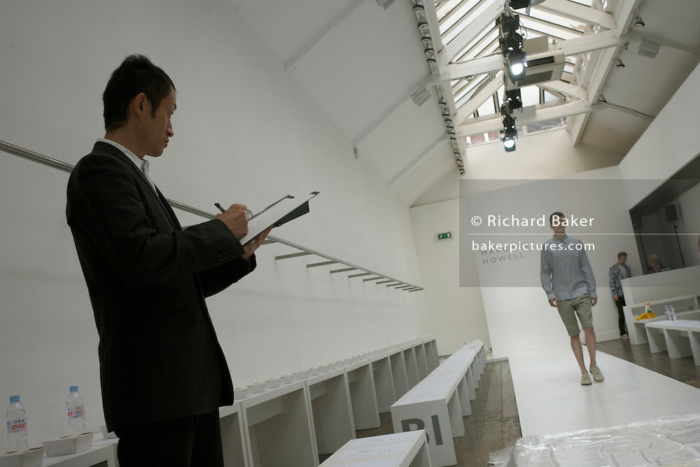 "A Japanese buyer watches a male model walk the catwalk of couturier Margaret Howell's Fashion Week show rehearsal in the company's retail flagship and design studio at 34 Wigmore Street, Central London England. Making notes on his clipboard as he looks at the striding man, the audience has yet to arrive so we see a largely empty scene that usually  serves as a shop. Howell is one of Britain's more understated of couture brands alongside more flamboyant personalities. Howell admits to being ""inspired by the methods by which something is made .. enjoying the tactile quality of natural fabrics such as tweeds, linen and cotton in a relaxed, natural and lived in look."""