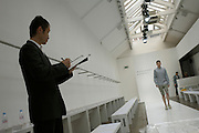 """A Japanese buyer watches a male model walk the catwalk of couturier Margaret Howell's Fashion Week show rehearsal in the company's retail flagship and design studio at 34 Wigmore Street, Central London England. Making notes on his clipboard as he looks at the striding man, the audience has yet to arrive so we see a largely empty scene that usually  serves as a shop. Howell is one of Britain's more understated of couture brands alongside more flamboyant personalities. Howell admits to being """"inspired by the methods by which something is made .. enjoying the tactile quality of natural fabrics such as tweeds, linen and cotton in a relaxed, natural and lived in look."""""""