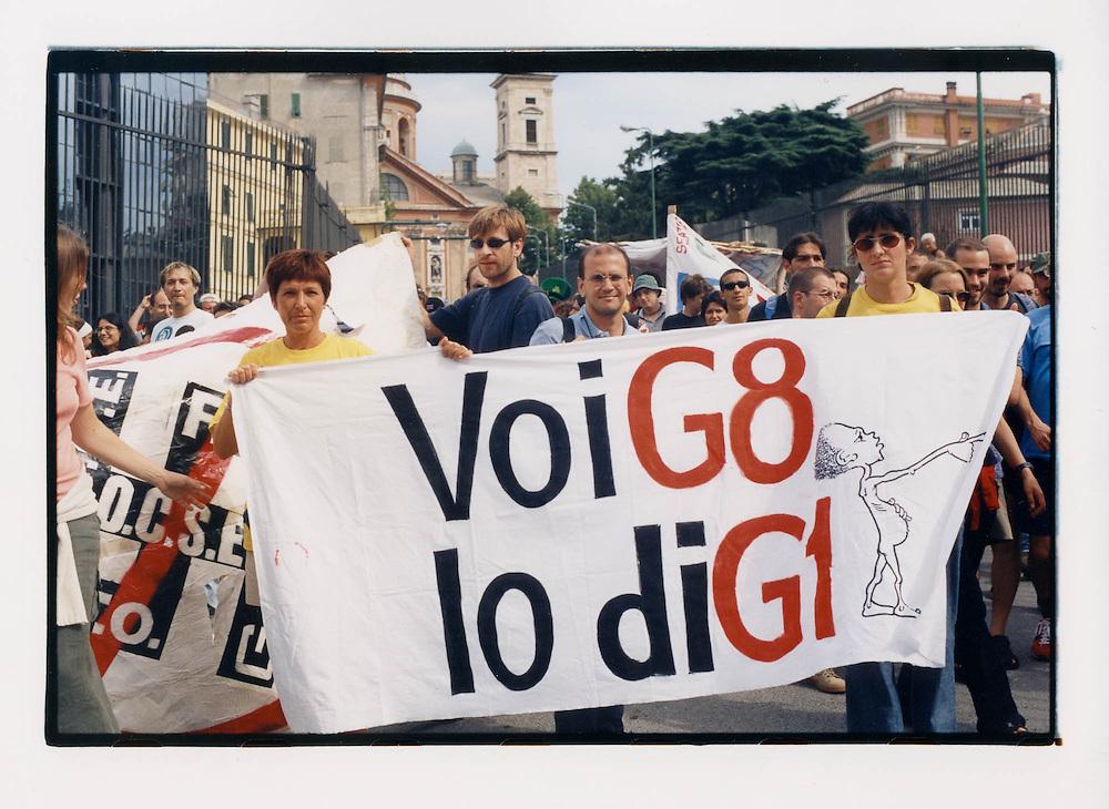 """Proteste contro il summit del G8, Genova luglio 2001. 19 luglio, corteo dei Migranti. Striscione """"Voi G8, Io diG1"""", indicativo della sensibilità dei movimenti verso il divario tra il nord e il sud del mondo."""