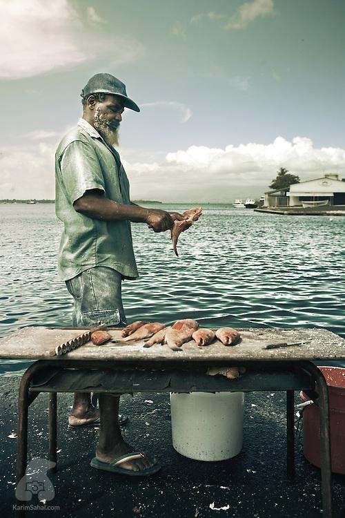 A fishmonger at 'La Darse' market in Pointe-à-Pitre, Guadeloupe.