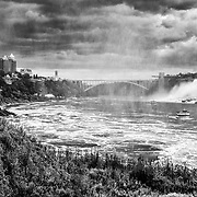 Dramatic image of Niagara Falls in black and white taken from behind the falls.