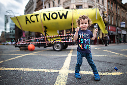 © Licensed to London News Pictures. 30/08/2019. Manchester, UK. SEB CHEUNG (two) in front of a boat with ACT NOW painted on the hull , placed in the centre of Deansgate . Extinction Rebellion block Deansgate in Manchester City Centre , at the start of several days of planned disruption organised by environmental campaigners . Manchester City Council has declared a climate emergency but activists say the council's development plans do not reflect this . Photo credit: Joel Goodman/LNP