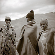 Three African men wrapped in traditional Lesotho blankets and knit hats, keep out the chill of the mountain morning. Lesotho is a land-locked country within South Africa, all above 6,000 ft. elevation.