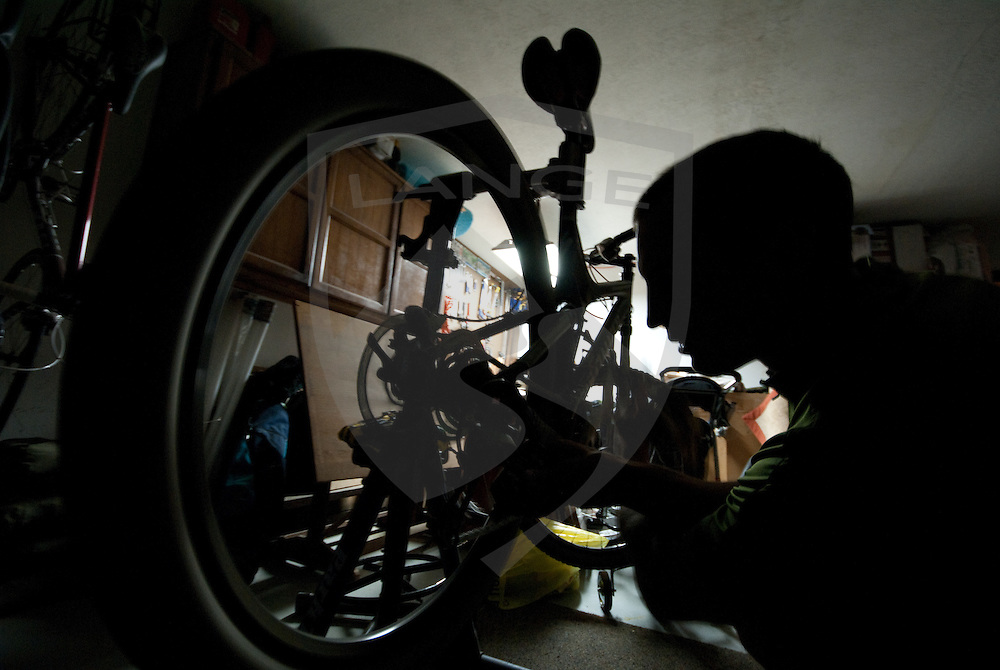 mountain biker cliff youngberg makes final adjustments to his rear derailleur at his garage workspace before heading out on a sunrise ride.