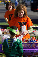 Middletown, New York  - A volunteer helps a child at the food table during the Halloween Fall Festival at the Middletown YMCA's Center for Youth Programs on Oct. 25, 2014.