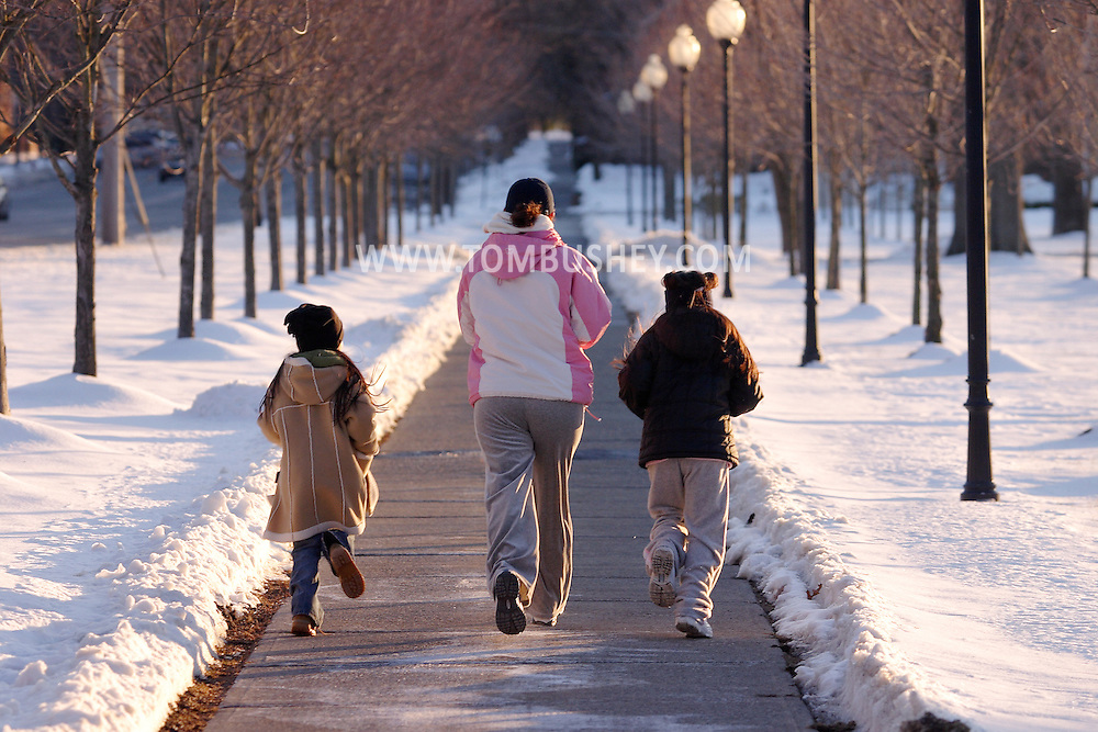 Goshen, N.Y. - A woman and two children run down the sidewalk on a late winter afternoon on March 4, 2006.