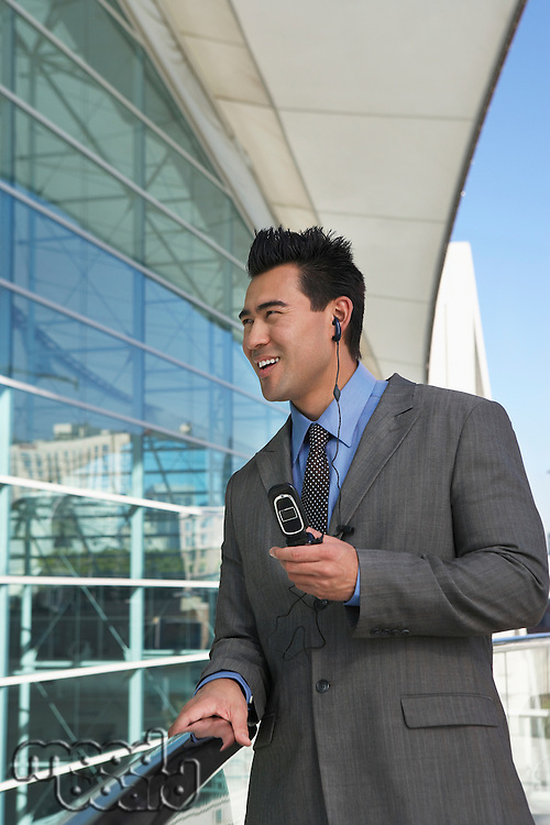 Businessman using mobile phone with earpiece office building