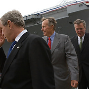 Pres. Bush, alongside former President George H W Bush and Florida (FL) Gov. Jeb Bush, walk after participating in the christening of CVN-77 George H W Bush aircraft carrier Saturday, October 7, 2006, in Newport News, Virginia (VA).  CVN-77 is the 10th and final of the Nimitz-class aircraft carriers.  It is set to replace the USS Kitty Hawk in 2008...Photo by Khue Bui