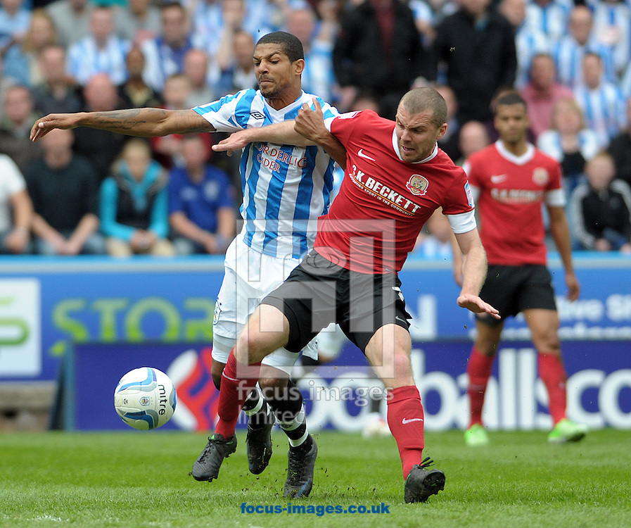 Picture by Graham Crowther/Focus Images Ltd +44 7763 140036.04/05/2013.Jermaine Beckford of Huddersfield Town battles with Stephen Dawson of Barnsley during the npower Championship match at the John Smiths Stadium, Huddersfield.