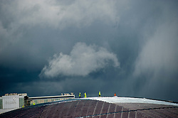 Workers in a rain storm on the roof of The Hydro construction on the site of the SECC (Scottish Exhibition and Conference Centre), Glasgow, Scotland, UK.