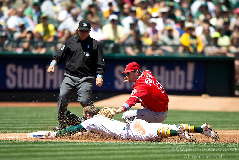 OAKLAND, CA - JUNE 21:  Brett Lawrie #15 of the Oakland Athletics is tagged out attempting to steal third base by David Freese #6 of the Los Angeles Angels of Anaheim in front of umpire Greg Gibson #53 during the second inning at O.co Coliseum on June 21, 2015 in Oakland, California. (Photo by Jason O. Watson/Getty Images) *** Local Caption *** Brett Lawrie; David Freese; Greg Gibson