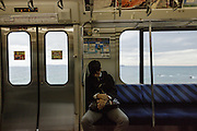 Chiba prefecture, December 17 2015 - A man asleep on the train with Tokyo bay in the background, on the way to Mont Nokogiri. Mount Nokogiri is one of major attractions of  Chiba prefecture, but not yet well known by foreign tourists.