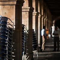 Piled up chairs under the arches of Plaza Mayor in the early morning, Salamanca, Spain