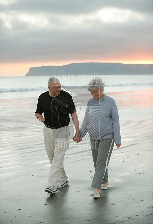 Senior couple enjoying a walk on a beach in California