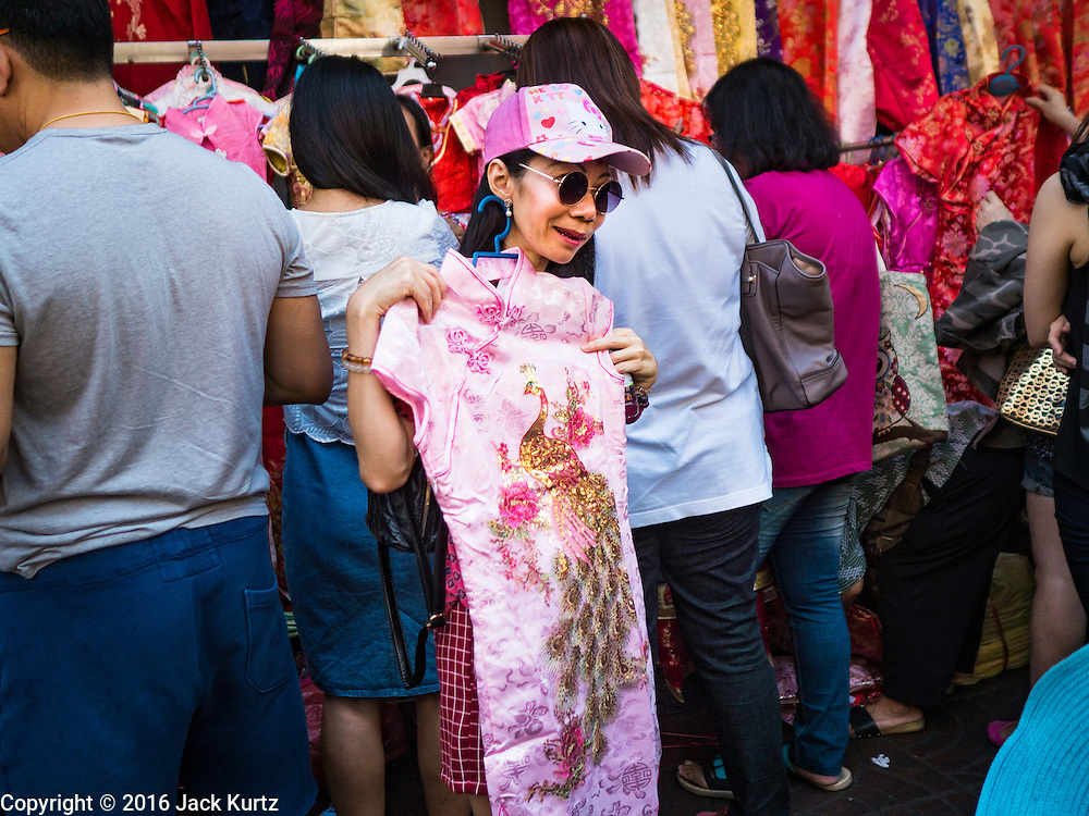 "31 JANUARY 2016 - BANGKOK, THAILAND: A woman shops for new clothes at a stand on Yaowarat Road, in Bangkok's Chinatown district, before the celebration of the Lunar New Year. Chinese New Year, also called Lunar New Year or Tet (in Vietnamese communities) starts Monday February 8. The coming year will be the ""Year of the Monkey."" Thailand has the largest overseas Chinese population in the world; about 14 percent of Thais are of Chinese ancestry and some Chinese holidays, especially Chinese New Year, are widely celebrated in Thailand.           PHOTO BY JACK KURTZ"