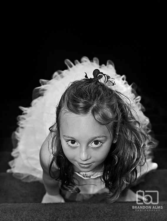 A flower girl looking up at the camera at a wedding.
