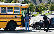 "Dillon Lane of Kennewick, right, talks with Kennewick police after colliding with a school bus in his 2001 Hyundai Elantra on Columbia Center Boulevard at 4th Avenue in Kennewick. Around 40 kids were on board from Desert Hills Middle School and Kamiakin High School. No one was hurt, ""just sore from the seatbelt kicking my ass,"" said Lane. Kennewick police Sgt. Ken Lattin said the bus driver was at fault since she was turning left, and she would be cited for failure to yield. Another school bus came to pick up kids who hadn't already called their parents and the this bus was able to drive away. ""School buses are built to take a hit like this,"" said Ethan Schwebke, transportation manager for Kennewick School District. ""The only thing they lose against is a semi or a train."""