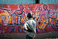 A boy in the Kibera slums of Nairobi looks at a mural calling for peaceful elections. Kibera was a hotspot for violence in 2007.